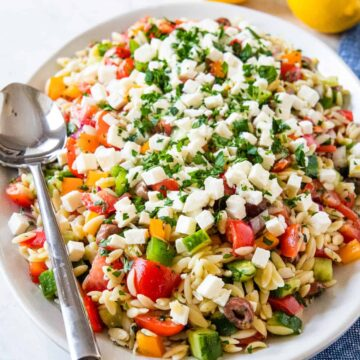 Greek orzo pasta salad shown on a serving platter.