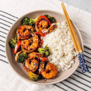 Overhead view of a bowl of honey garlic shrimp stir fry served with steamed rice.