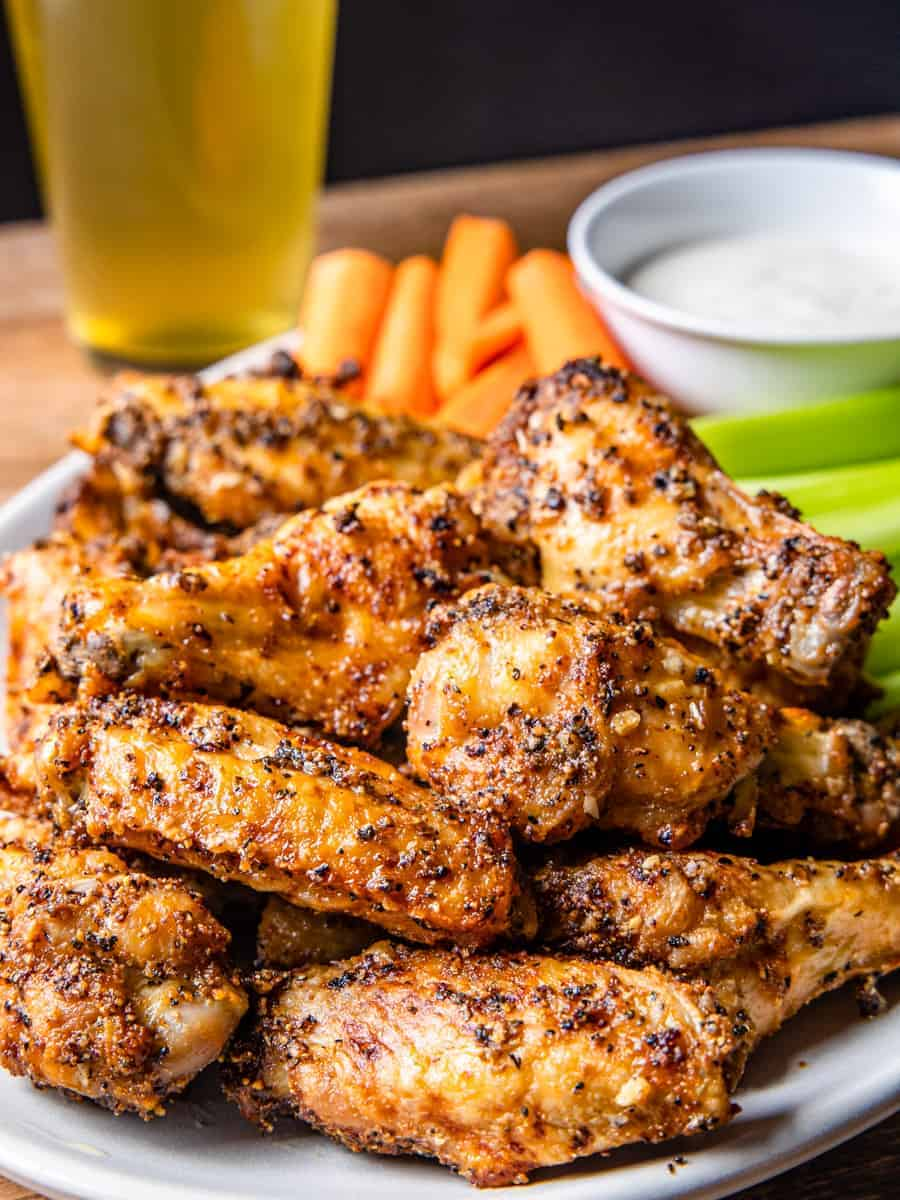 Side angle view of a large platter of lemon pepper chicken wings, served with celery, carrots, and dip.