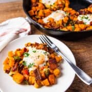 Sweet potato hash topped with an egg, set beside a skillet of sweet potatoes and eggs.