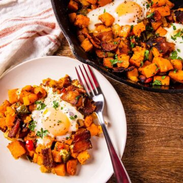 Sweet potato breakfast skillet wit eggs and bacon, served on a dish set next to a cast iron skillet.