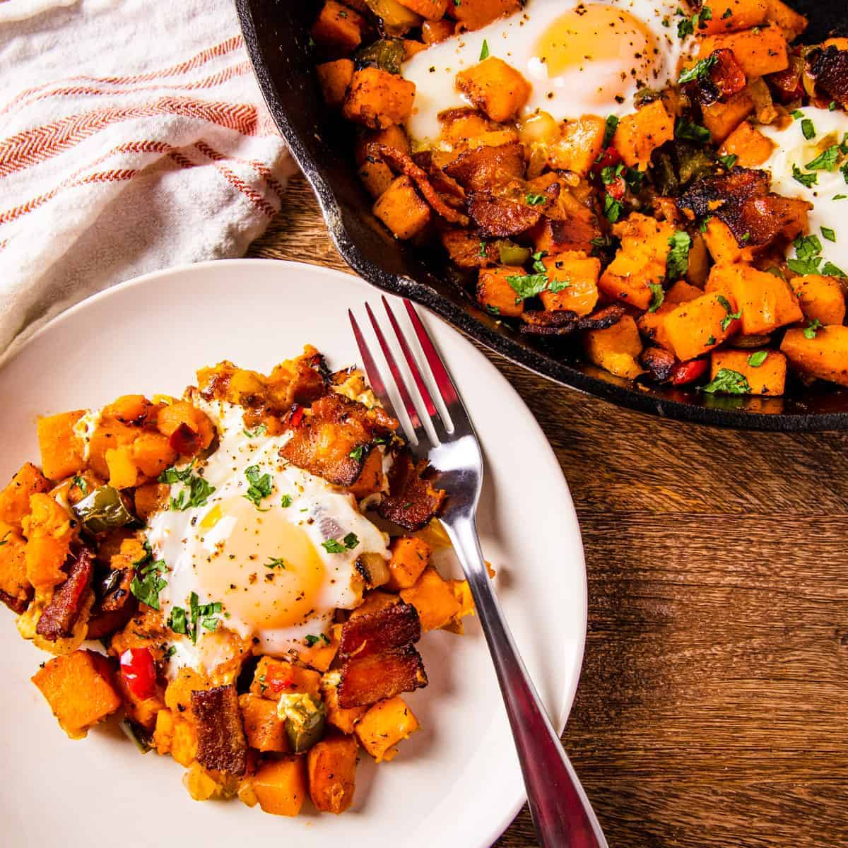 Sweet potatoes with eggs and bacon, served on a dish set next to a cast iron skillet.