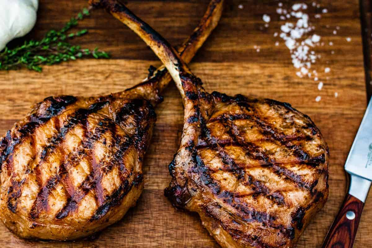Grilled pork chops shown on a cutting board.