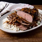 London broil shown on a bed of rice topped with mushroom and onion gravy.