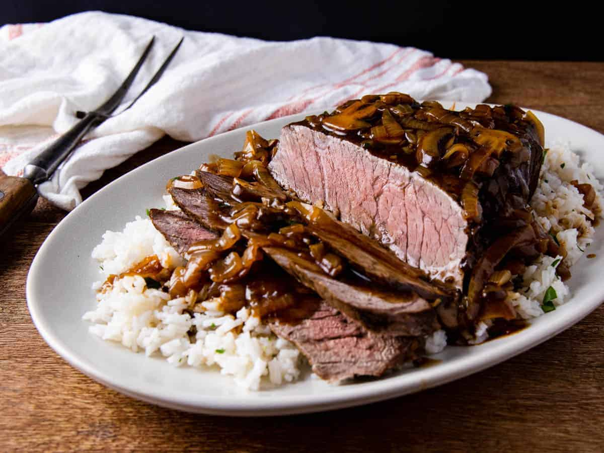 London broil served on a bed of rice topped with mushroom and onion gravy.