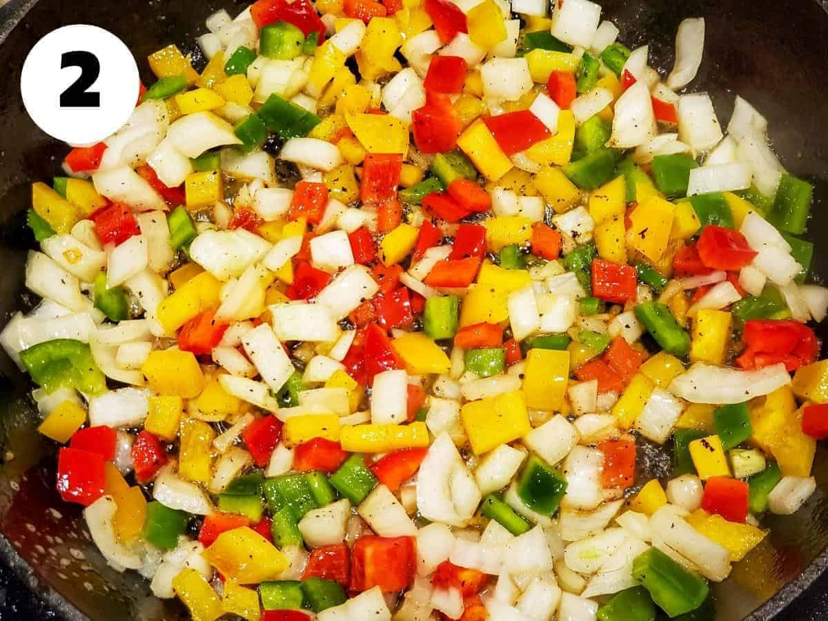Onions and peppers cooking in a skillet.