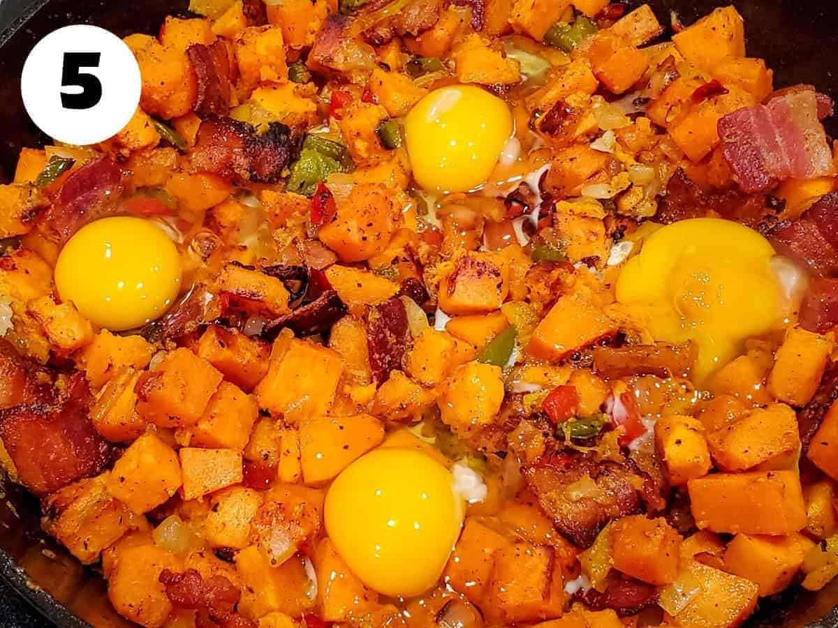Bacon added back to the sweet potato hash with fresh cracked eggs overtop.