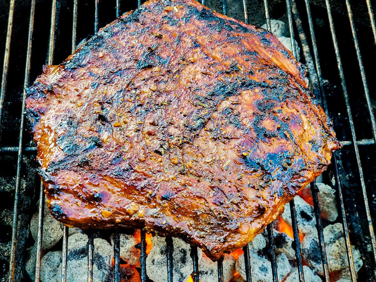 Flank steak shown cooking on a grill.