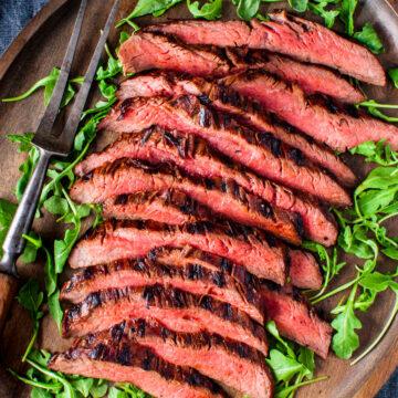 Grilled flank steak served on a platter.