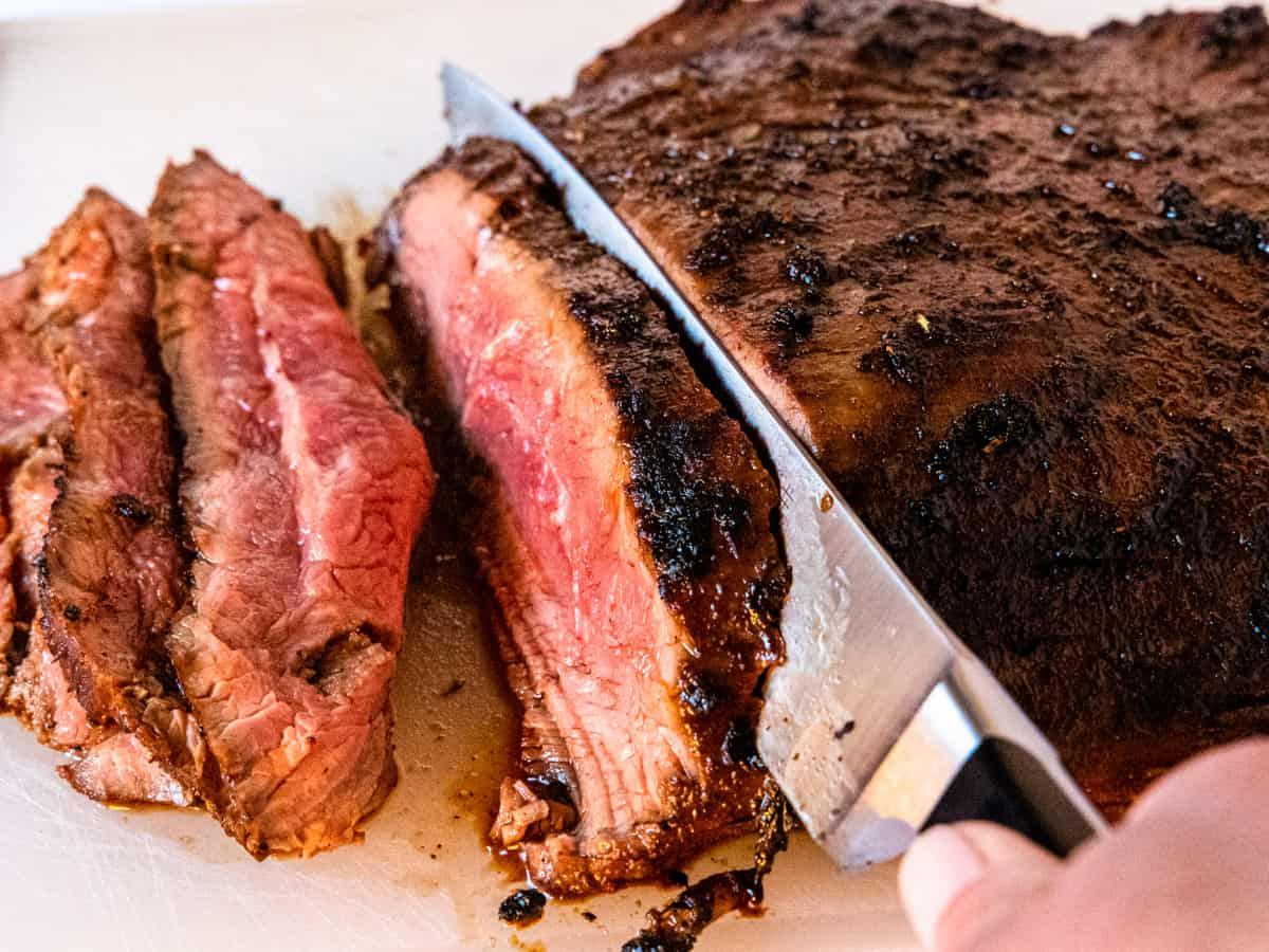 Flank Steak being sliced thinly across the grain.