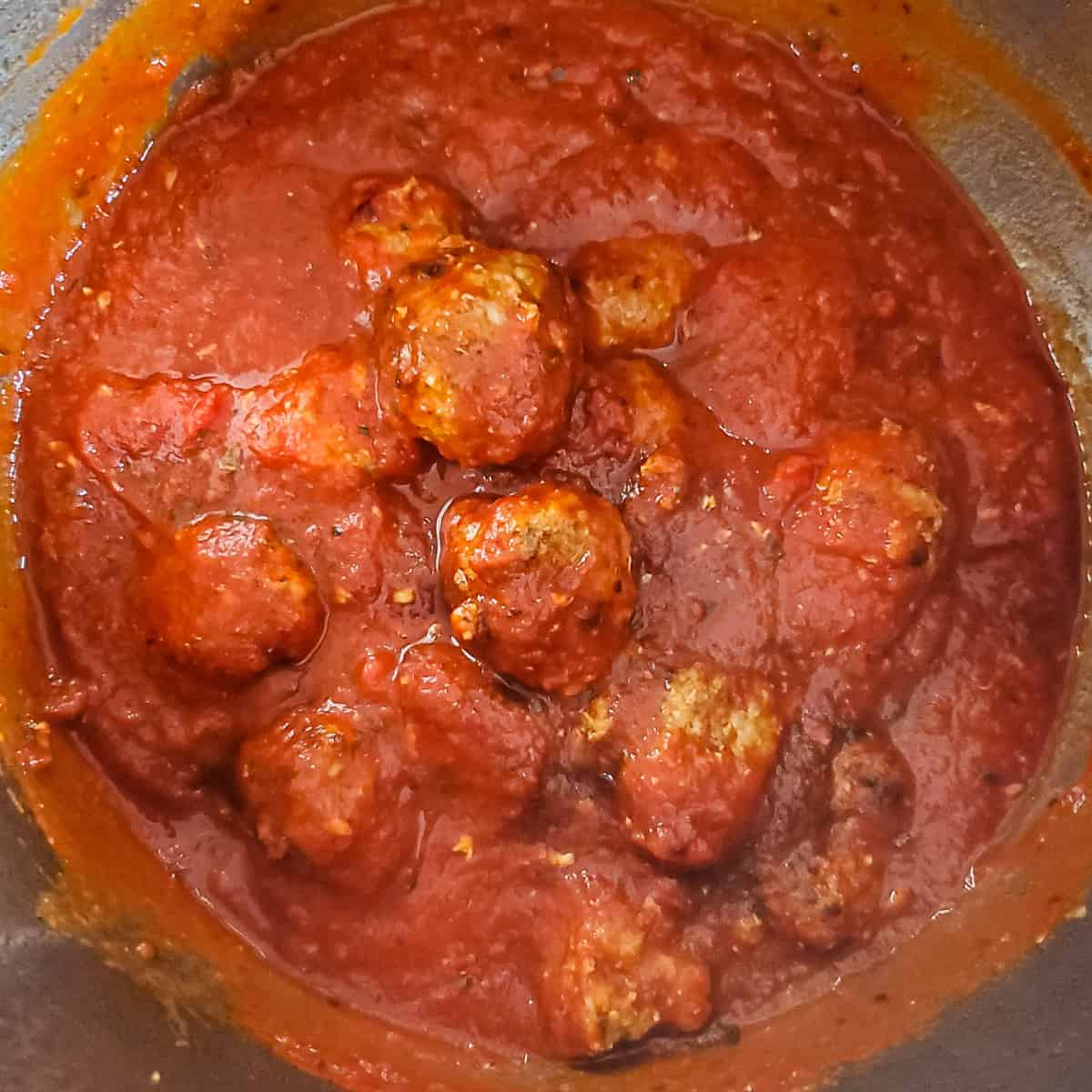 Meatballs and sauce shown in an Instant Pot prior to pressure cooking.