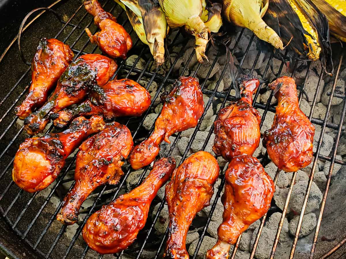 Chicken legs coaed with barbecue sauce being cooked on a grill.