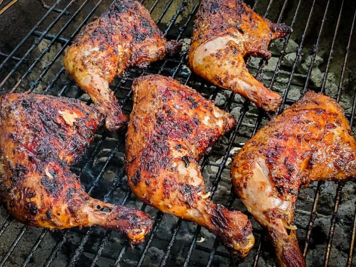 Chicken leg quarters shown on a grill.