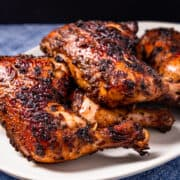 Grilled jerk chicken leg quarters served on a platter.