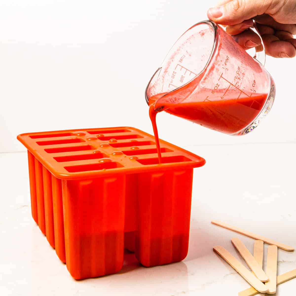The strawberry mixture is shown being poured into the popsicle mold.