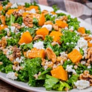 Side angle view of a large serving platter piled high with kale and roasted butternut squash salad.